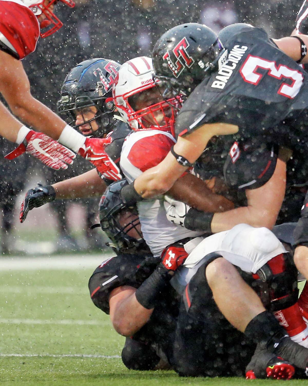 Katy' Deondrick Glass is smothered by tacklers including Lake Travis?' Ty Badciong on top. Katy football game against Lake Travis in the semifinals of the Class 6A, Division I football playoffs on Saturday, December 16, 2017 at Alamo Stadium.