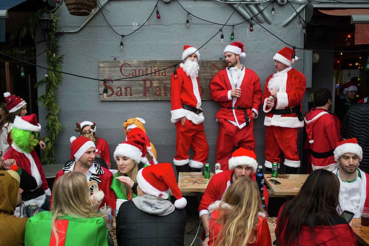 Santas drink in the dry weather outside Cantina de San Patricio during SantaCon 2017 in downtown Seattle on Saturday, Dec. 16, 2017.