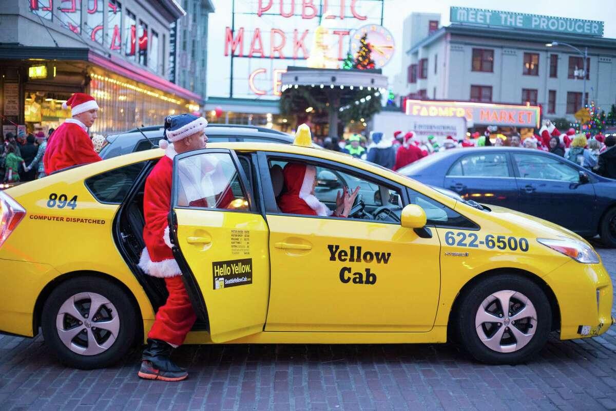 Santas climb into a taxi after photos at Pike Place Market.