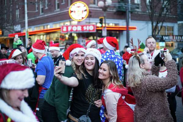 SantaCon attendees congregate at Pike Place Market for a group photo during SantaCon 2017 in downtown Seattle on Saturday, Dec. 16, 2017.