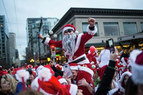 A pirate Santa sits on someone's shoulders during photographs at Pike Place Market during SantaCon 2017 in downtown Seattle on Saturday, Dec. 16, 2017.