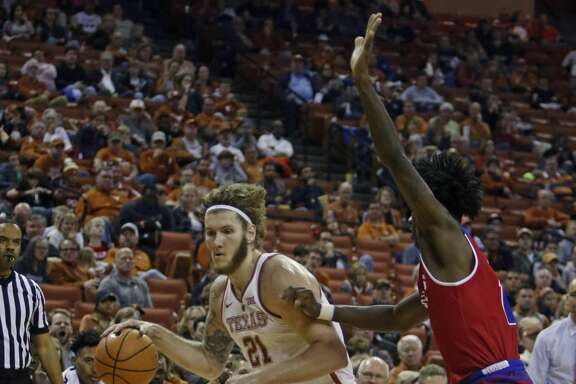 Texas forward Dylan Osetkowski (21) drives to the basket against Louisiana Tech forward Anthony Duruji during the second half of an NCAA college basketball game, Saturday, Dec. 16, 2017, in Austin, Texas. Texas won 75-60. (AP Photo/Michael Thomas)