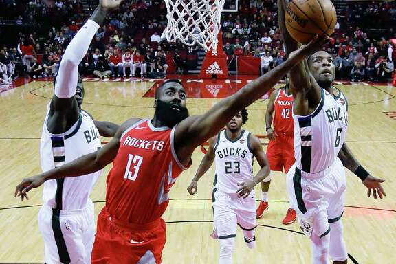 Rockets guard James Harden (13) drives between Bucks center Thon Maker, left, and guard Eric Bledsoe on his way to scoring a game-high 31 points on 8-for-21 shooting.