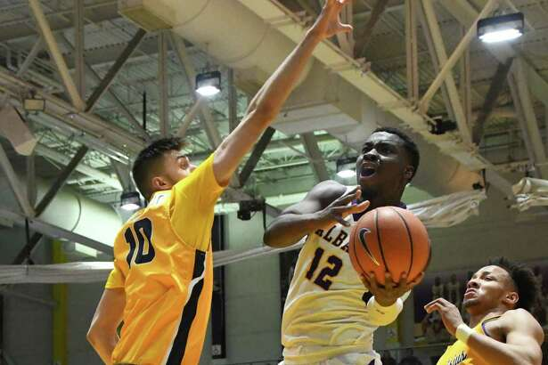 University of Albany forward Devonte Campbell jumps for a shot as Canisius center Selvedin Planincic attempts to block the shot during a non-conference game on Saturday, Dec. 16, 2017, in Albany, N.Y. UAlbany rallied against Canisius for a decisive 68-65 victory. (Jenn March/Special to the Times Union)