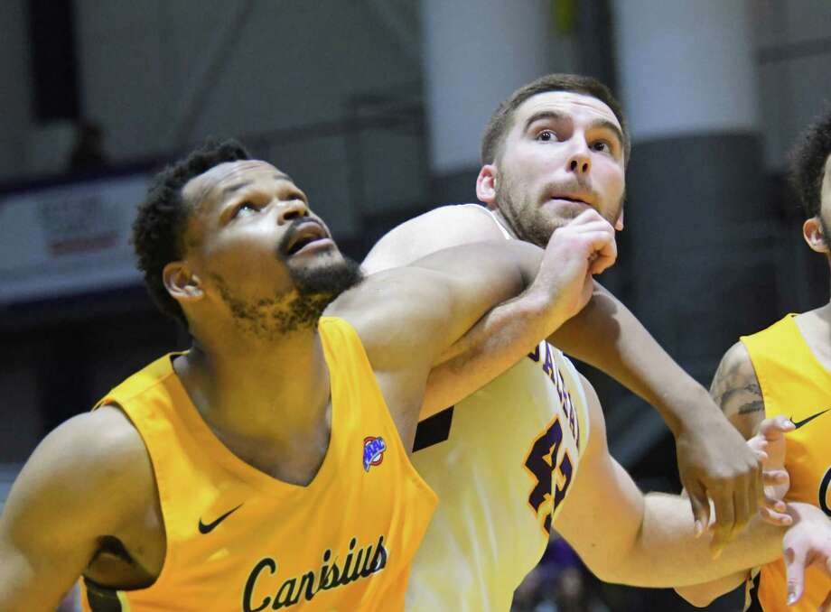 University of Albany forward Greig Stire and Canisius forward Jermaine Crumpton push against each other as they watch the rebound following a Albany foul shot during a non-conference game on Saturday, Dec. 16, 2017, in Albany, N.Y. UAlbany rallied against Canisius for a decisive 68-65 victory. (Jenn March/Special to the Times Union) Photo: Jenn March / 20042313A