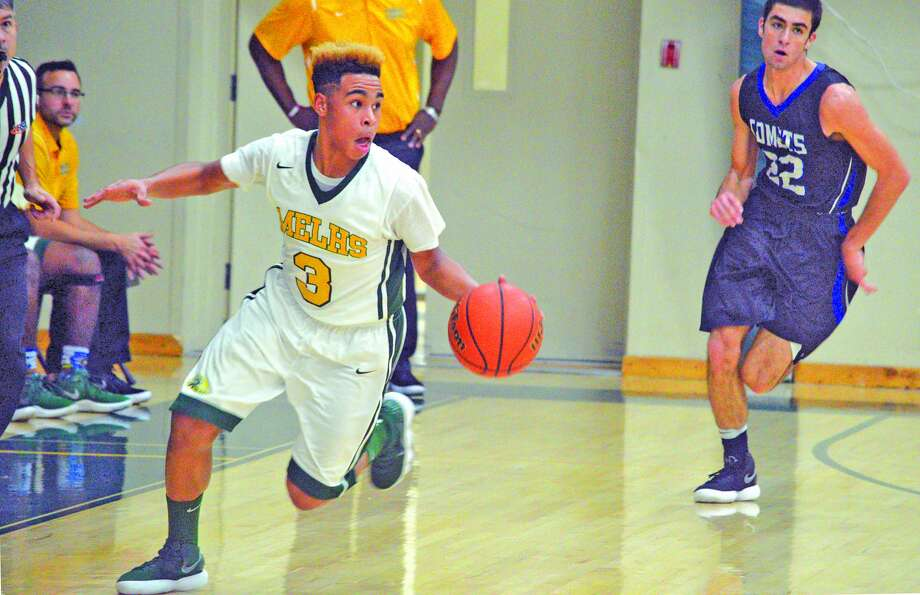 Metro-East Lutheran junior Jason Williams, left, brings the ball up the court during the second quarter of Saturday's home game against Greenville.