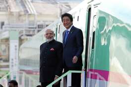 Indian Prime Minister Narendra Modi (left), and Shinzo Abe, Japan's prime minister, leave a bullet train during a visit to a plant of Kawasaki Heavy Industries Ltd.'s Rolling Stock Co. in Kobe, Japan, on Nov. 12, 2016.
