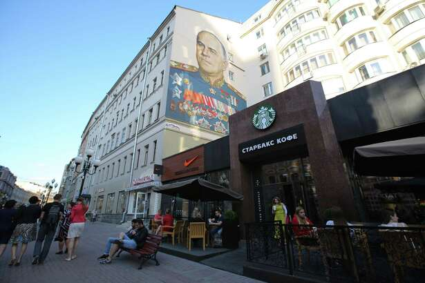 A wall mural, depicting Russian General Georgy Zhukov, a World War II Soviet hero, sits on a building above a Nike sportswear store and a Starbucks coffee shop in Moscow on June 8, 2015.