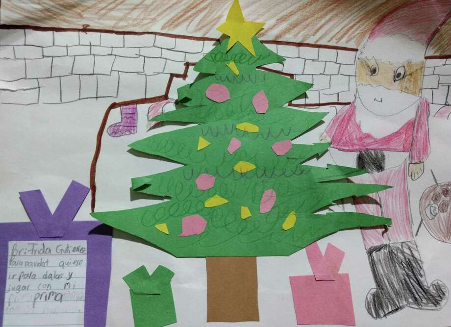 Frida Gutierrez of Dayton created a Christmas scene to accompany her letter to Santa. Her artwork shows Santa standing by the Christmas tree and coming down the chimney. She also remembered to put out milk and cookies for the Man in Red. Photo: Submitted