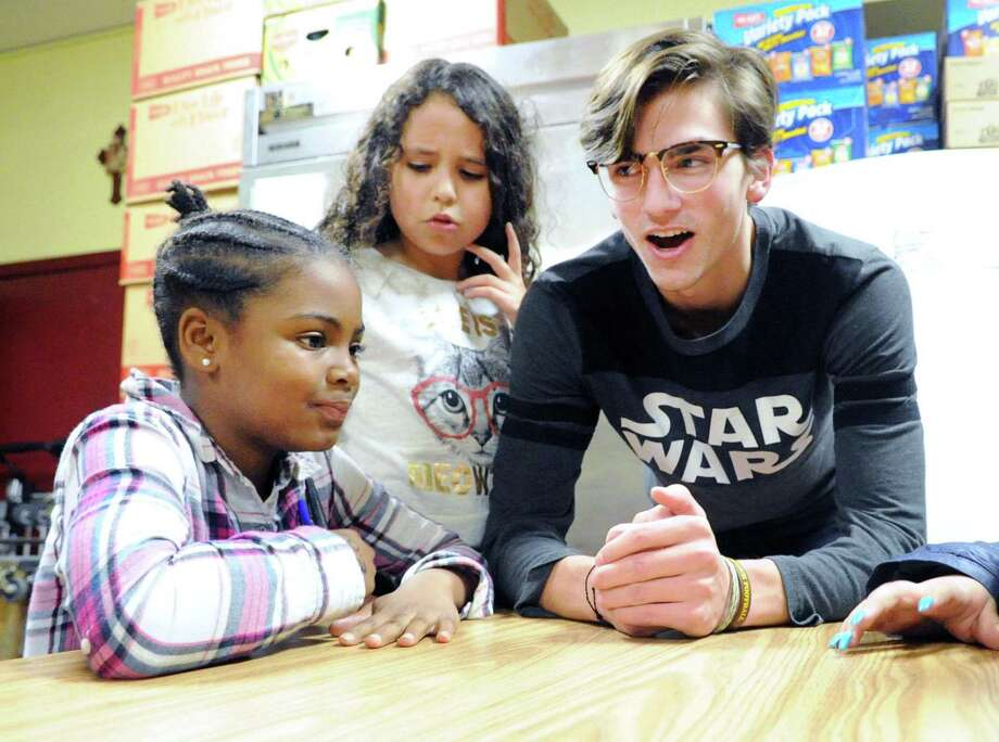 "Don Bosco Center youth service award winner Sebastian Cobb, 18, a Brunswick School senior, right, with Destini Furman, 10, left, and Katelyn Valenzuela, 9, during the ""Dinner Buddies"" program at the Don Bosco Center in Port Chester, N.Y., Thursday night, Dec. 15, 2017. Photo: Bob Luckey Jr. / Hearst Connecticut Media / Greenwich Time"