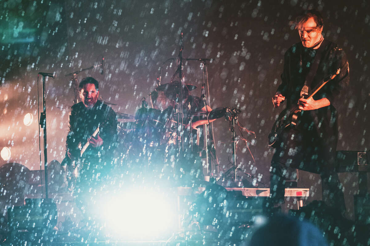 Trent Reznor and Nine Inch Nails play in the rain at Day for Night, 2018. >>The artwork at Day for Night