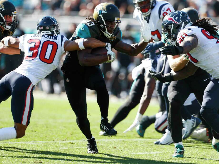 Jacksonville Jaguars running back Chris Ivory (33) runs between ]Houston Texans cornerback Kevin Johnson (30) and outside linebacker Jadeveon Clowney (90) during the first quarter of an NFL football game at EverBank Field on Sunday, Dec. 17, 2017, in Jacksonville. Photo: Brett Coomer, Houston Chronicle / © 2017 Houston Chronicle