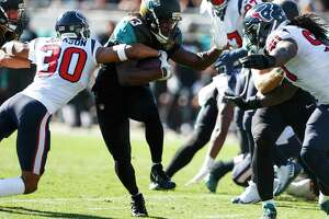 Jacksonville Jaguars running back Chris Ivory (33) runs between ]Houston Texans cornerback Kevin Johnson (30) and outside linebacker Jadeveon Clowney (90) during the first quarter of an NFL football game at EverBank Field on Sunday, Dec. 17, 2017, in Jacksonville.