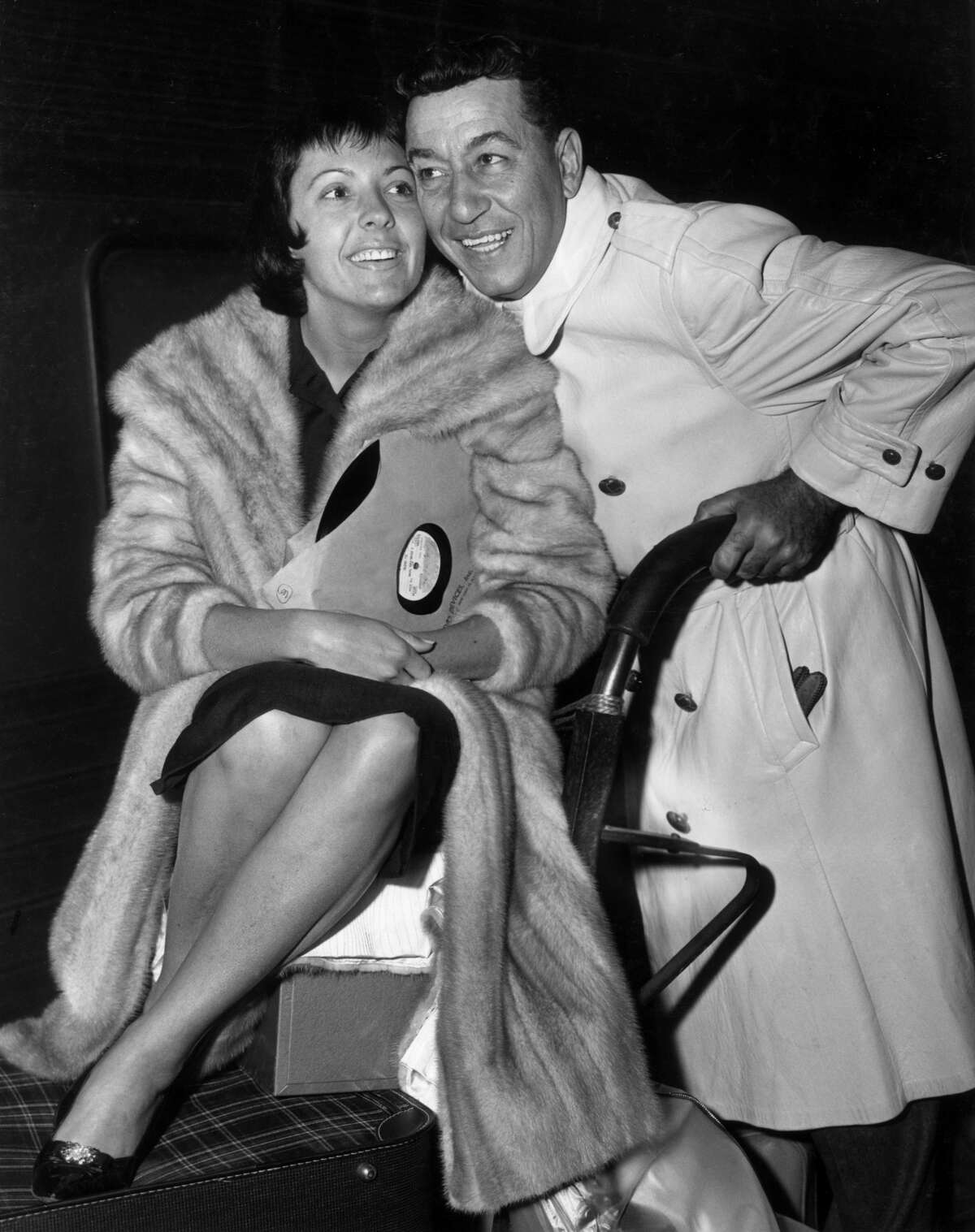 circa 1945: American jazz trumpeter and bandleader Louis Prima (1911 - 1978) smiles as he pushes a luggage cart carrying his wife, American singer Keely Smith. She wears a long fur coat and holds a copy of her hit single, 'I Wish You Love.'