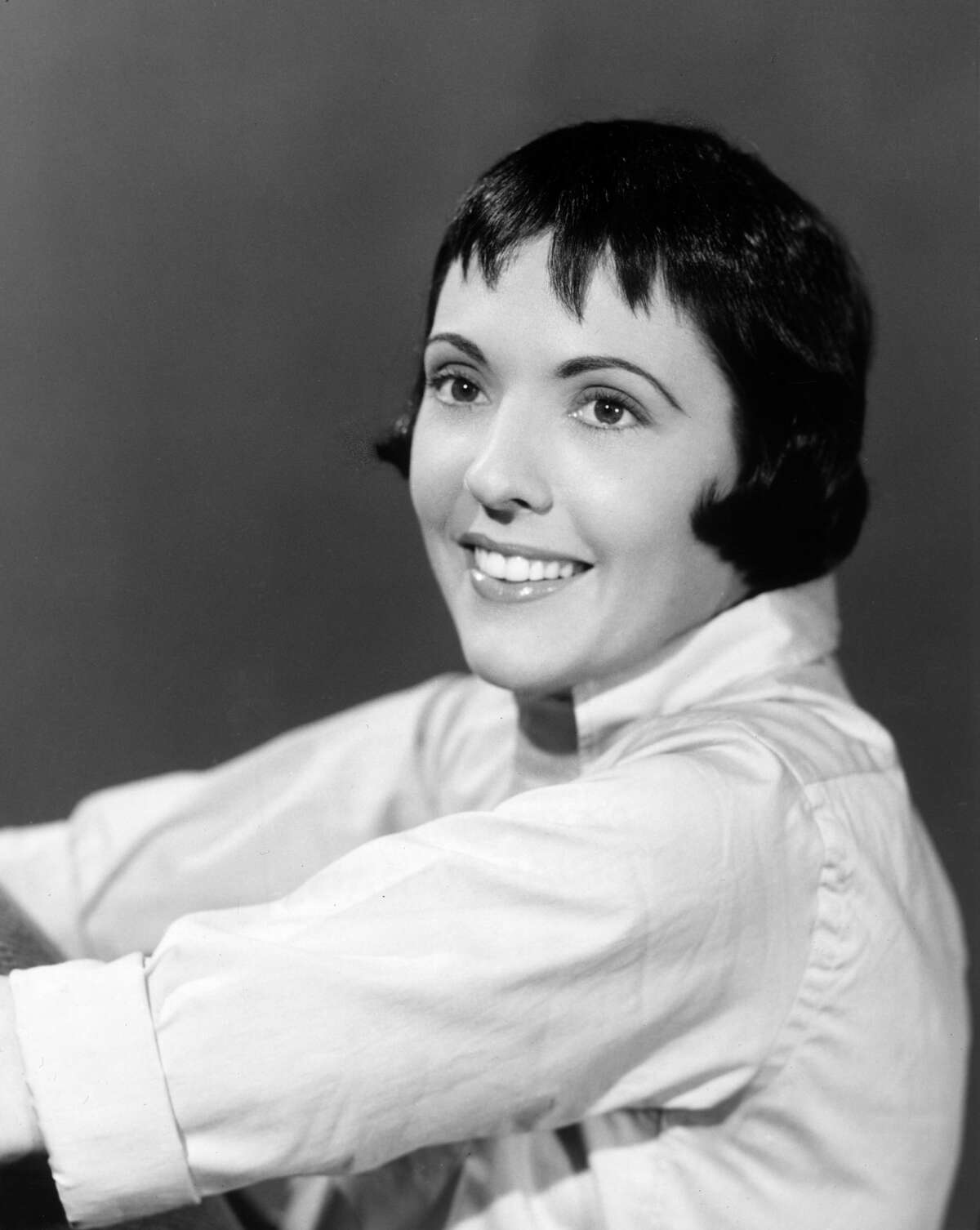 circa 1955: Studio headshot portrait of American singer Keely Smith smiling in an oxford shirt.