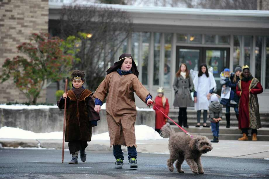 Shepherds Knox Belton, left, and John Carroll walk toward the manger with dog Ellis during the annual Live Nativity performance outside the First United Methodist Church on Cross Road in Stamford, Conn. on Sunday, Dec. 17, 2017. Photo: Michael Cummo / Hearst Connecticut Media / Stamford Advocate