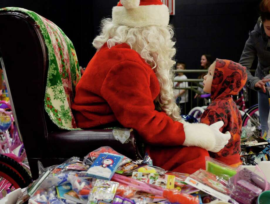 Alexander Lamont looks up at Santa at the Sheriff's Hometown Christmas party on Sunday, Dec. 17, 2017, in Voorheesville, N.Y.  The Sheriff's Department began helping 29 years ago with one family.  This year the department, through the generosity of the community, helped 190 children have gifts for Christmas.   (Paul Buckowski / Times Union) Photo: PAUL BUCKOWSKI, Albany Times Union / 20042434A