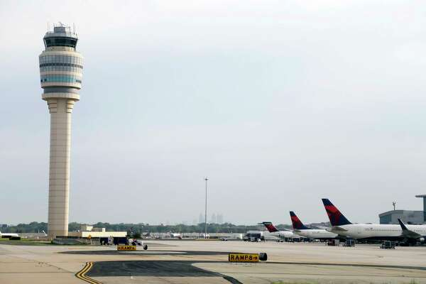 FILE- This May 9, 2016, file photo, shows an air traffic control tower at their gates at Hartsfield–Jackson Atlanta International Airport in Atlanta. Authorities say a power outage at the Hartsfield-Jackson Atlanta International Airport has disrupted ingoing and outgoing flights. Airport spokesman Reese McCraine says the outage occurred early Sunday, Dec. 17, 2017. He says all airport operations are being affected and that outgoing flights were halted. (AP Photo/Mike Stewart, File)