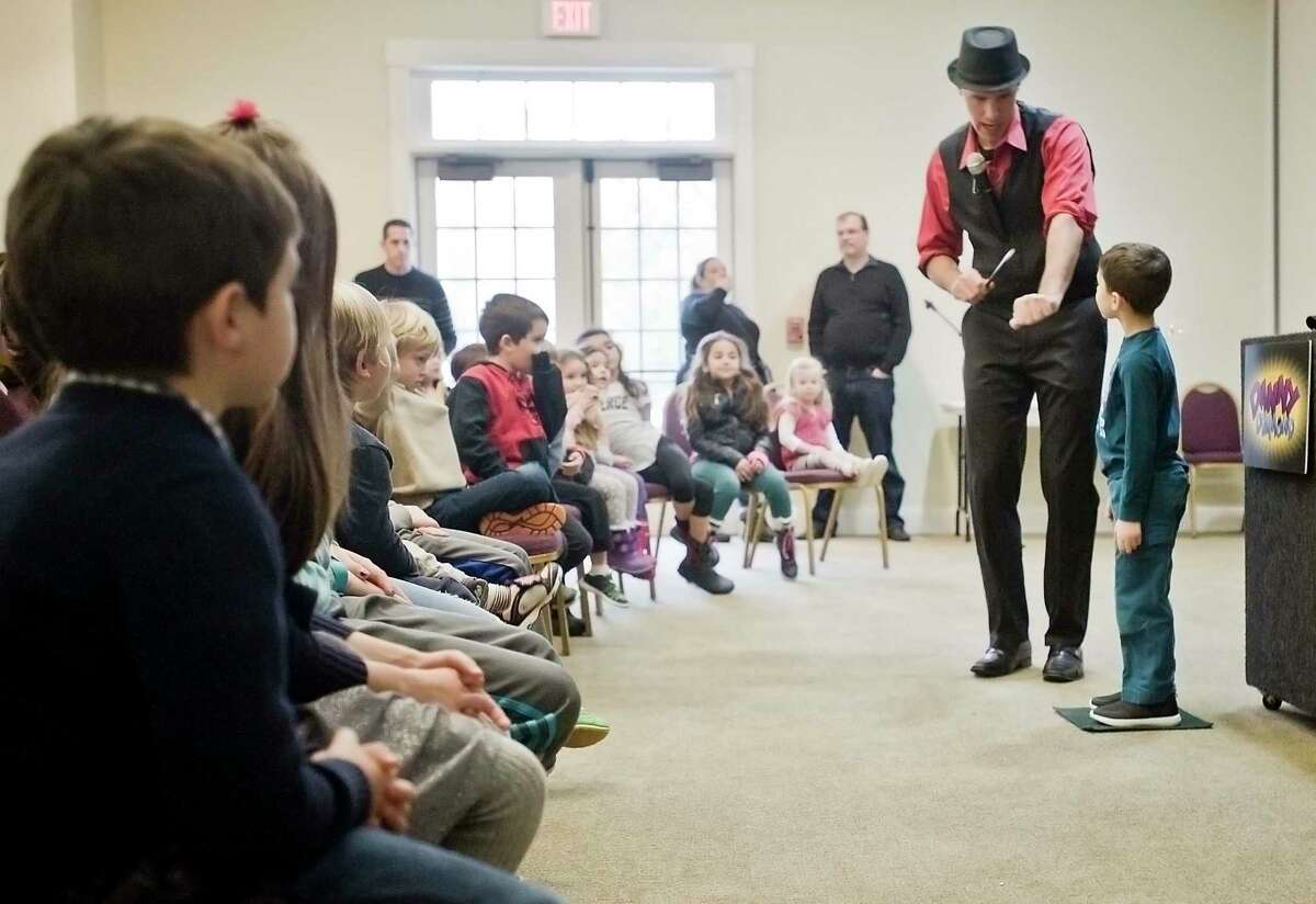 Kids participate in tricks by magician Danny Diamond at a Hanukkah event hosted by the Early Childhood Center of Congregation Shir Shalom in Ridgefield. Sunday, Dec. 17, 2017