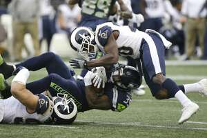 Seattle Seahawks running back Mike Davis is tackled by Los Angeles Rams outside linebacker Connor Barwin, left, and free safety Lamarcus Joyner, right, in the first half of an NFL football game, Sunday, Dec. 17, 2017, in Seattle. (AP Photo/Elaine Thompson)