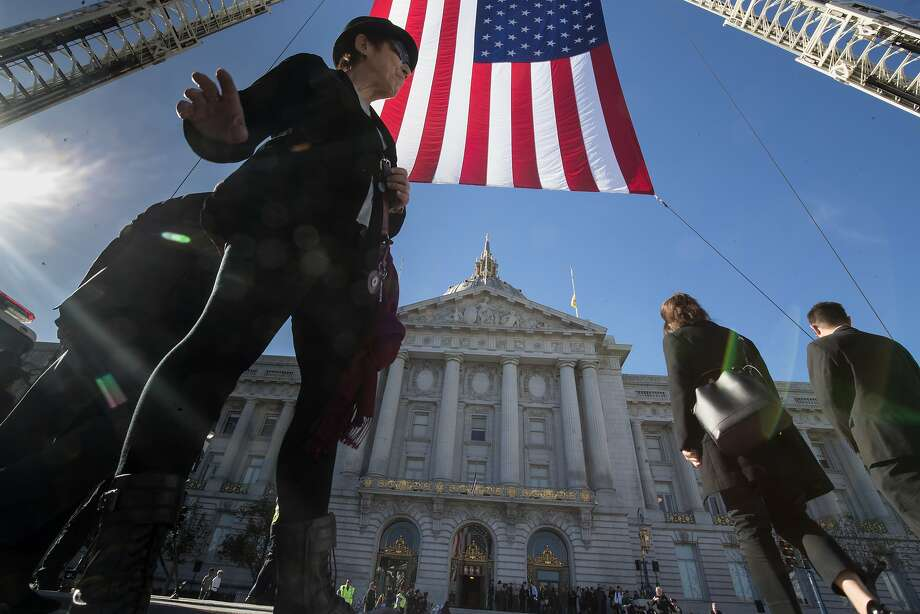 Dede Moriaty waits to cross to attend Mayor Ed Lee's memorial service in City Hall on Sunday. Photo: Paul Kuroda, Special To The Chronicle