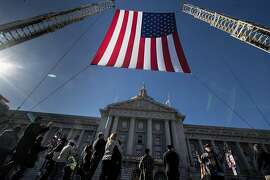People wait to cross the street to attend Mayor Ed Lee's funeral at Civic Center Plaza on Sunday, Dec. 17, 2017 in San Francisco, CA.