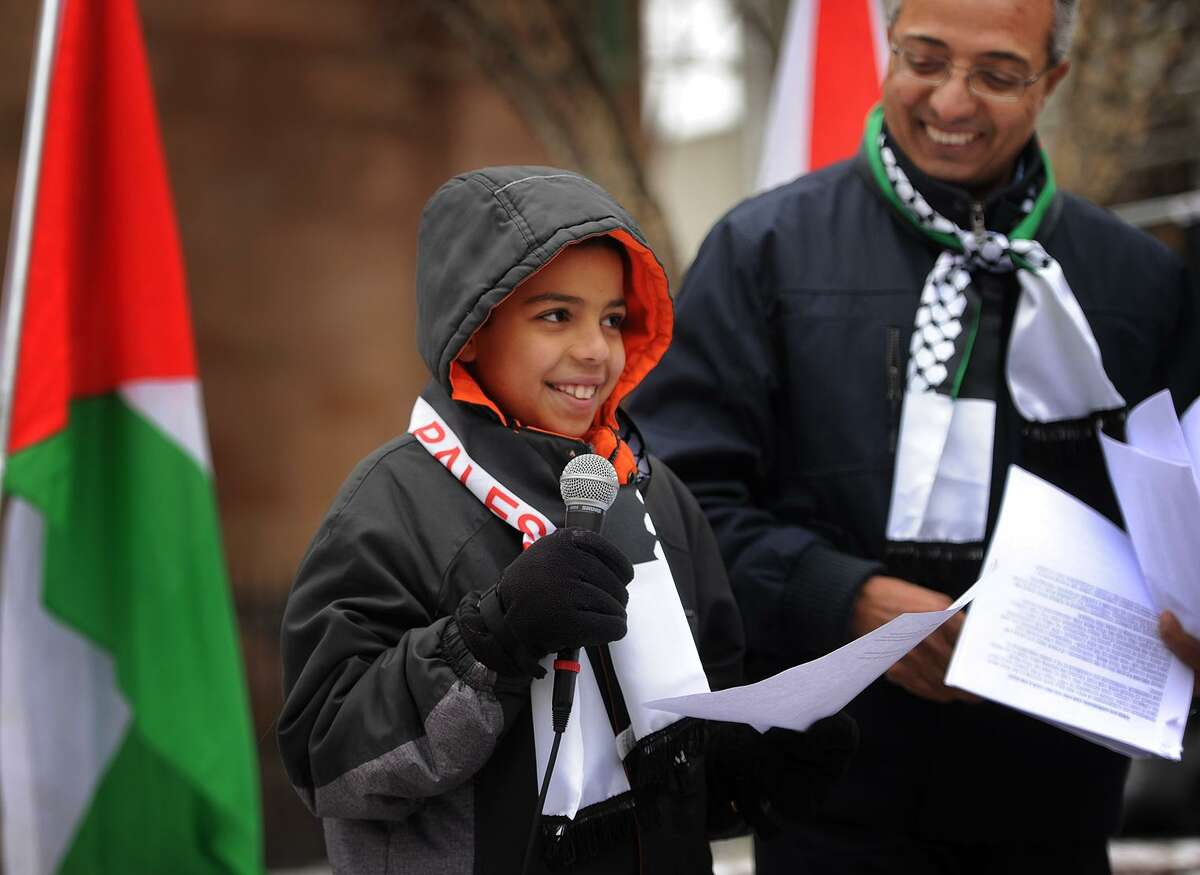 Yahia Hassan, 10, of Fairfield, speaks at a rally against the declaration declaring Jerusalem the capital of Israel on McLevy Green in Bridgeport on Sunday,. At right is Ahmed Ebrahim, president of the Bridgeport Islamic Community Center.