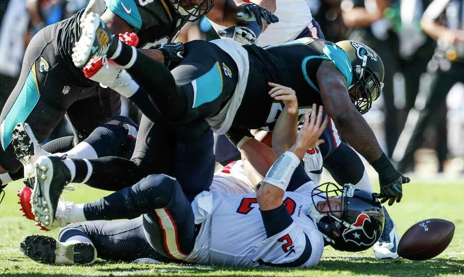 Houston Texans quarterback T.J. Yates (2) loses the football as he is sacked by Jacksonville Jaguars defensive tackle Malik Jackson (97) during the first quarter of an NFL football game at EverBank Field on Sunday, Dec. 17, 2017, in Jacksonville. ( Brett Coomer / Houston Chronicle ) Photo: Brett Coomer, Staff / © 2017 Houston Chronicle
