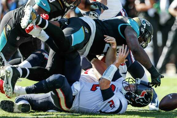 Houston Texans quarterback T.J. Yates (2) loses the football as he is sacked by Jacksonville Jaguars defensive tackle Malik Jackson (97) during the first quarter of an NFL football game at EverBank Field on Sunday, Dec. 17, 2017, in Jacksonville. ( Brett Coomer / Houston Chronicle )