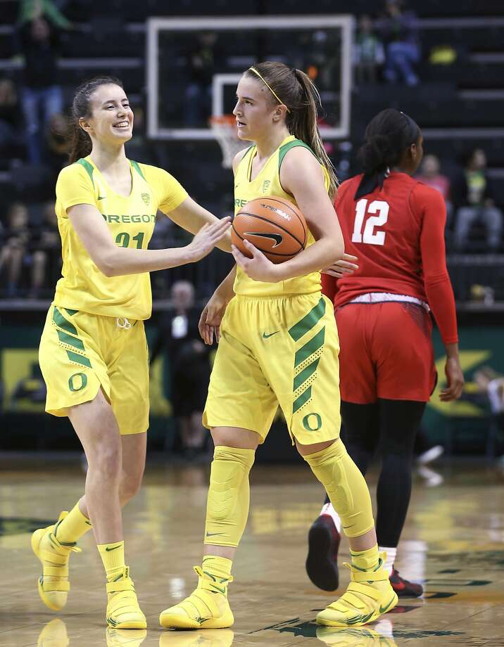 Oregon's Sabrina Ionescu (right) is congratulated by teammate Aina Ayuso after pulling down a rebound to complete her seventh triple-double. Photo: Chris Pietsch, Associated Press