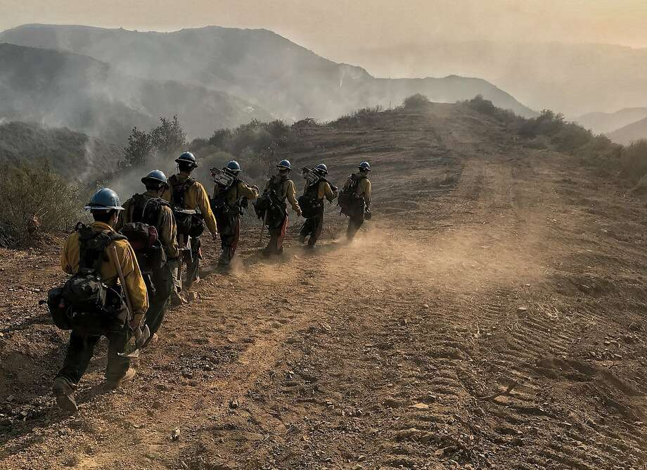 A crew heads down a fire break in Santa Barbara. The fire has spread to about 423 square miles. Photo: Mike Eliason, Associated Press