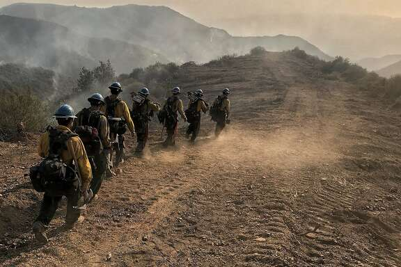In this photo provided by the Santa Barbara County Fire Department, U.S. Forest Service Hot Shot crew members from Ojai, Calif., head down a fire break to work off E. Camino Cielo in Santa Barbara, Calif., Sunday morning, Dec. 17, 2017. Thousands of firefighters tried Sunday to shield coastal communities from one of the biggest wildfires in California history while a funeral procession rolled past burn-scarred hillsides in honor of one of their colleagues who was killed battling the flames. (Mike Eliason/Santa Barbara County Fire Department via AP)