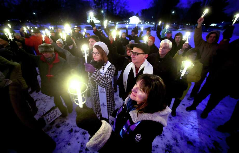 Rev. Ginger Brasher-Cunningham (bottom center) of First Congregational Church in Guilford raises a candle with others during a moment of silence at a vigil to commemorate the Sandy Hook tragedy and all victims and survivors of gun violence on the Madison Green on December 17, 2017. Photo: Arnold Gold / Hearst Connecticut Media / New Haven Register