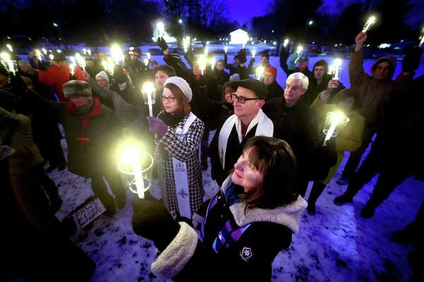 Rev. Ginger Brasher-Cunningham (bottom center) of First Congregational Church in Guilford raises a candle with others during a moment of silence at a vigil to commemorate the Sandy Hook tragedy and all victims and survivors of gun violence on the Madison Green on December 17, 2017.