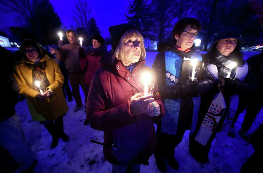 Kathryn Westgard of Guilford (center) participates with others in a moment of silence at a vigil to commemorate the Sandy Hook tragedy and all victims and survivors of gun violence on the Madison Green on December 17, 2017. Photo: Arnold Gold / Hearst Connecticut Media / New Haven Register