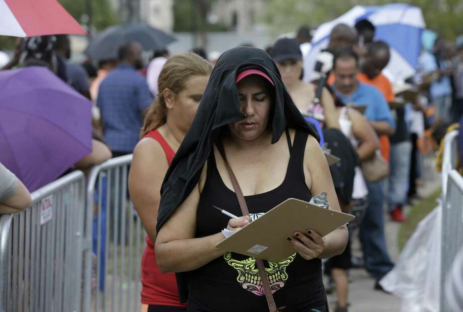 People fill out an application for the state's Disaster Supplemental Nutrition Assistance Program as they wait in line outside the Southwest Multi-Service Center, 6400 High Star, Wednesday, Oct. 4, 2017, in Houston. People were given the forms near the front entrance. Thousands of people waited in a long line around the block to apply for D-SNAP, a short-term food assistance benefits to families recovering from a disaster. Three months after Harvey, poor and minority communities are still struggling to rebuild from a storm that disproportionately affected them, and which worsened chronic issues related to inequality, according to a report released last week by the Kaiser Family Foundation and the Episcopal Health Foundation. Photo: Melissa Phillip /Houston Chronicle / © 2017 Houston Chronicle