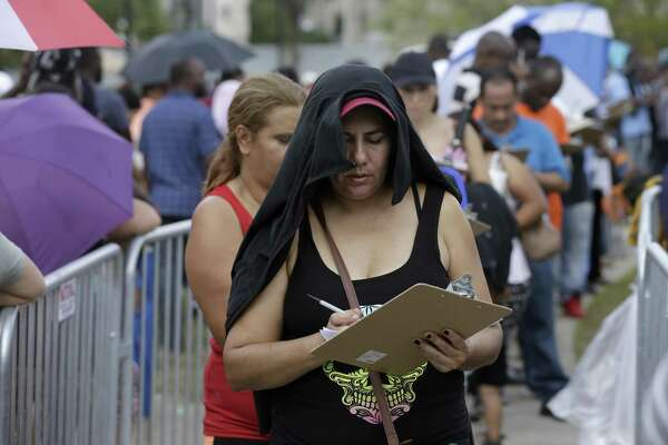 People fill out an application for the state's Disaster Supplemental Nutrition Assistance Program as they wait in line outside the Southwest Multi-Service Center, 6400 High Star, Wednesday, Oct. 4, 2017, in Houston. People were given the forms near the front entrance. Thousands of people waited in a long line around the block to apply for D-SNAP, a short-term food assistance benefits to families recovering from a disaster. Three months after Harvey, poor and minority communities are still struggling to rebuild from a storm that disproportionately affected them, and which worsened chronic issues related to inequality, according to a report released last week by the Kaiser Family Foundation and the Episcopal Health Foundation.