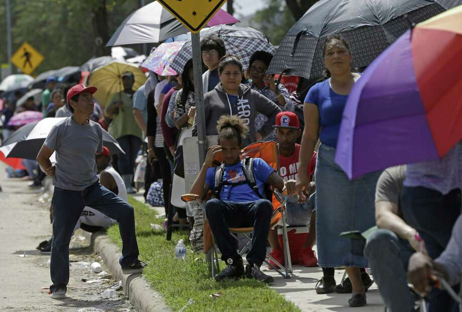 People wait in line to apply for the state's Disaster Supplemental Nutrition Assistance Program down the street from the Southwest Multi-Service Center, 6400 High Star, Wednesday, Oct. 4, 2017, in Houston. Thousands of people waited in a long line around the block to apply for D-SNAP, a short-term food assistance benefits to families recovering from a disaster. Three months after Harvey, poor and minority communities are still struggling to rebuild from a storm that disproportionately affected them, and which worsened chronic issues related to inequality, according to a report released last week by the Kaiser Family Foundation and the Episcopal Health Foundation. Photo: Melissa Phillip /Houston Chronicle / © 2017 Houston Chronicle