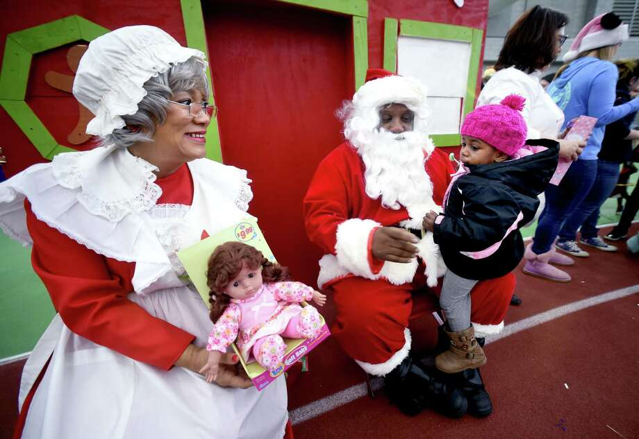 New Haven Mayor Toni Harp, dressed as Mrs. Claus, prepares to give Makiyrah Newton, 2, of New Haven a doll as she sits on the lap of New Haven Fire Chief John Alston, dressed as Santa Claus, during the Winter Wonderland Holiday Event & Coat Distribution at the Floyd Little Athletic Center in New Haven on December 17, 2017. Photo: Arnold Gold / Hearst Connecticut Media / New Haven Register
