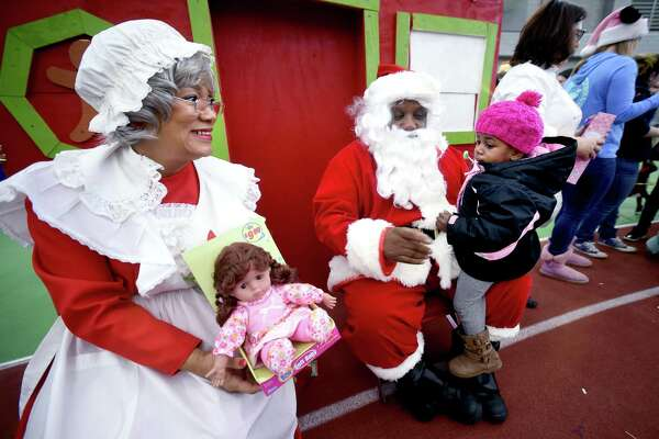 New Haven Mayor Toni Harp, dressed as Mrs. Claus, prepares to give Makiyrah Newton, 2, of New Haven a doll as she sits on the lap of New Haven Fire Chief John Alston, dressed as Santa Claus, during the Winter Wonderland Holiday Event & Coat Distribution at the Floyd Little Athletic Center in New Haven on December 17, 2017.