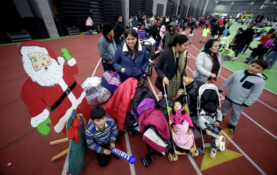 Families wait in line for gifts from Santa and Mrs. Claus at the Winter Wonderland Holiday Event & Coat Distribution at the Floyd Little Athletic Center in New Haven on December 17, 2017. Photo: Arnold Gold / Hearst Connecticut Media / New Haven Register