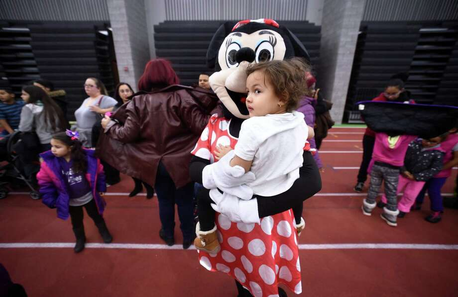 Minnie Mouse holds Miliana Espada, 2, of New Haven at the Winter Wonderland Holiday Event & Coat Distribution at the Floyd Little Athletic Center in New Haven on December 17, 2017. Photo: Arnold Gold / Hearst Connecticut Media / New Haven Register