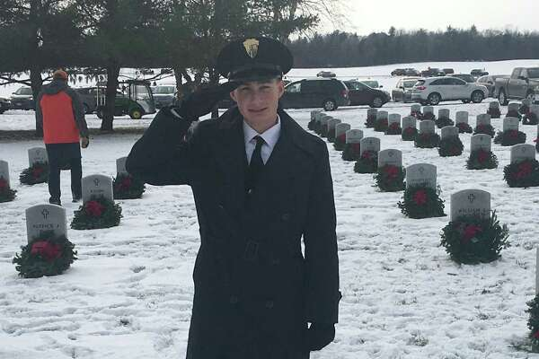 Evan Ryan of Christian Brothers Academy joins members of the school?s hockey team who laid wreaths on grave sites at Saratoga National Cemetery on Saturday. The event was part of the Wreaths Across America ceremony. Evan stands here at the grave of his grandfather.  (Provided photo)