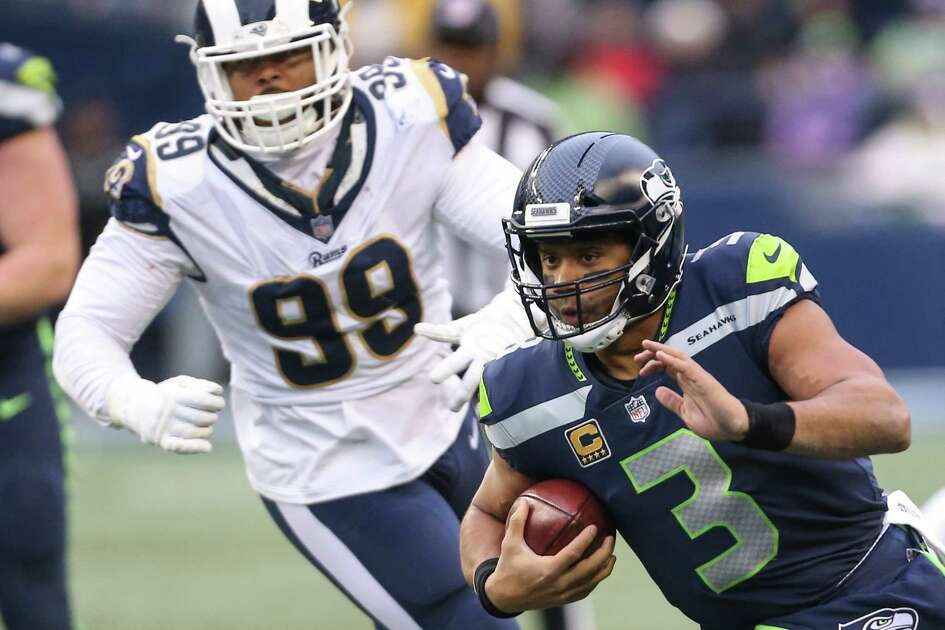 Seahawks quarterback Russell Wilson scrambles for a first down during the second half of a football game against the Los Angeles Rams at CenturyLink Field on Sunday, Dec. 17, 2017.