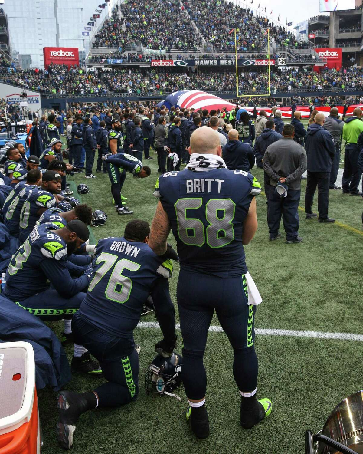 Seahawks offensive lineman Justin Britt stands with players kneeling in protest of police brutality and racial inequality during the national anthem before playing the Los Angeles Rams at CenturyLink Field on Sunday, Dec. 17, 2017.