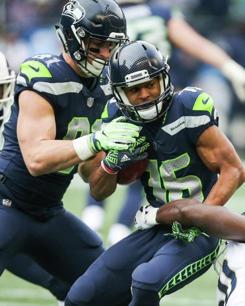 Seahawks tight end Nick Vannett attempts to help wide receiver Tyler Lockett hold onto the football as he's tackled during the first half of a football game against the Los Angeles Rams at CenturyLink Field on Sunday, Dec. 17, 2017.