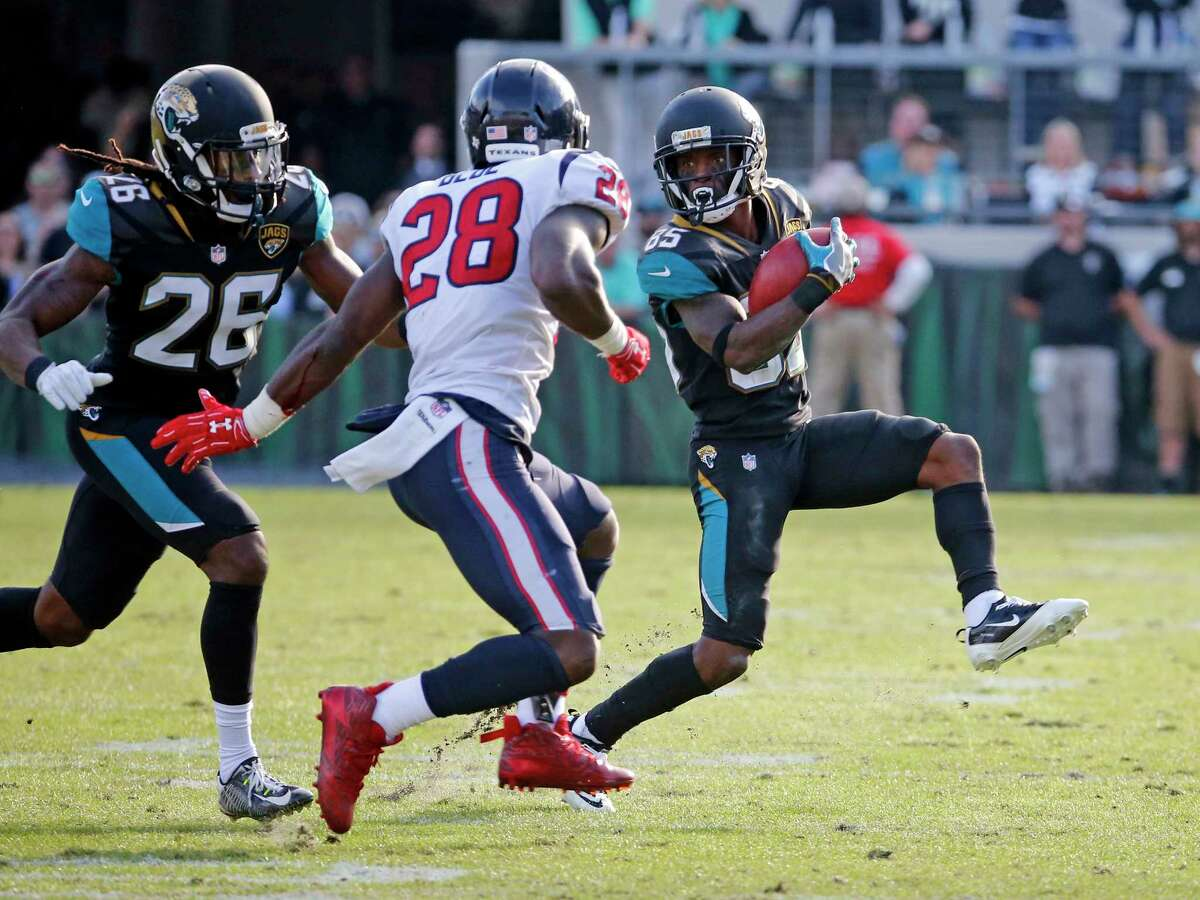 Jacksonville Jaguars' Jaydon Mickens (85) tries to get around Houston Texans' Alfred Blue (28) as Jaguars Jarrod Wilson (26) comes in to black on a punt return during the second half of an NFL football game, Sunday, Dec. 17, 2017, in Jacksonville, Fla. (AP Photo/Stephen B. Morton)