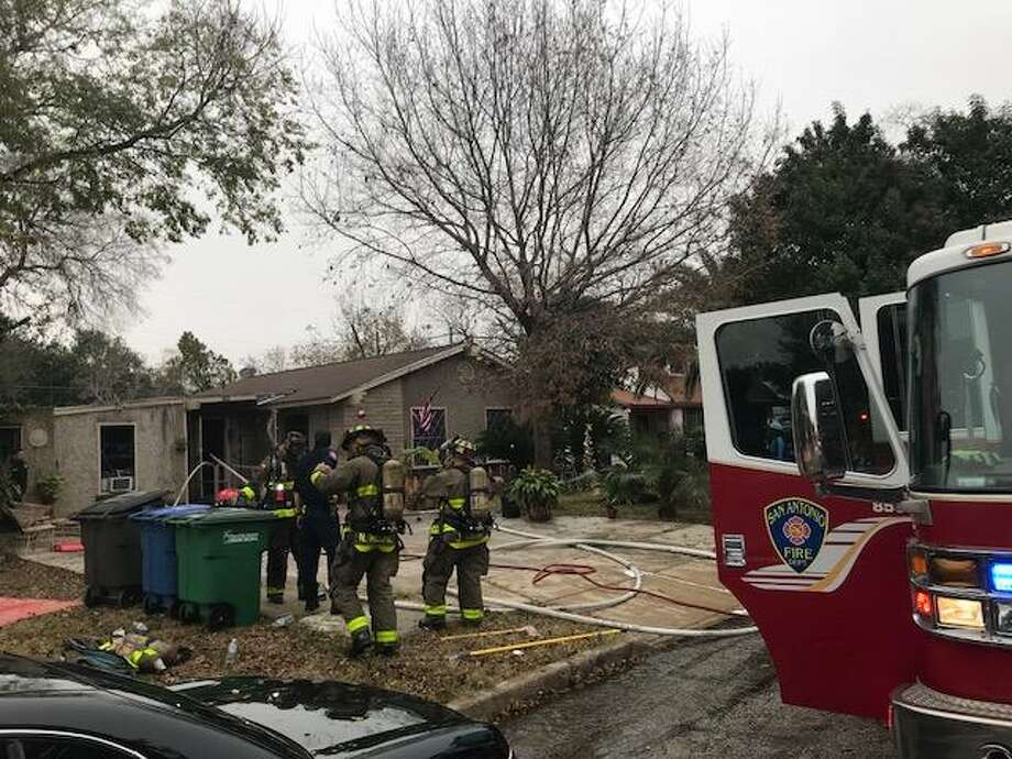 Firefighters do clean-up work Sunday afternoon Dec. 17, 2017 after extinguishing a fire at an East Side home in the 4100 block of Scarlet Oak Drive. The fire was started by a tipped-over gas can, San Antonio Fire officials said. Photo: Alexandro Luna, Staff / San Antonio Express-News / © 2017 San Antonio Express-News