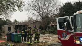 Firefighters do clean-up work Sunday afternoon Dec. 17, 2017 after extinguishing a fire at an East Side home in the 4100 block of Scarlet Oak Drive. The fire was started by a tipped-over gas can, San Antonio Fire officials said.