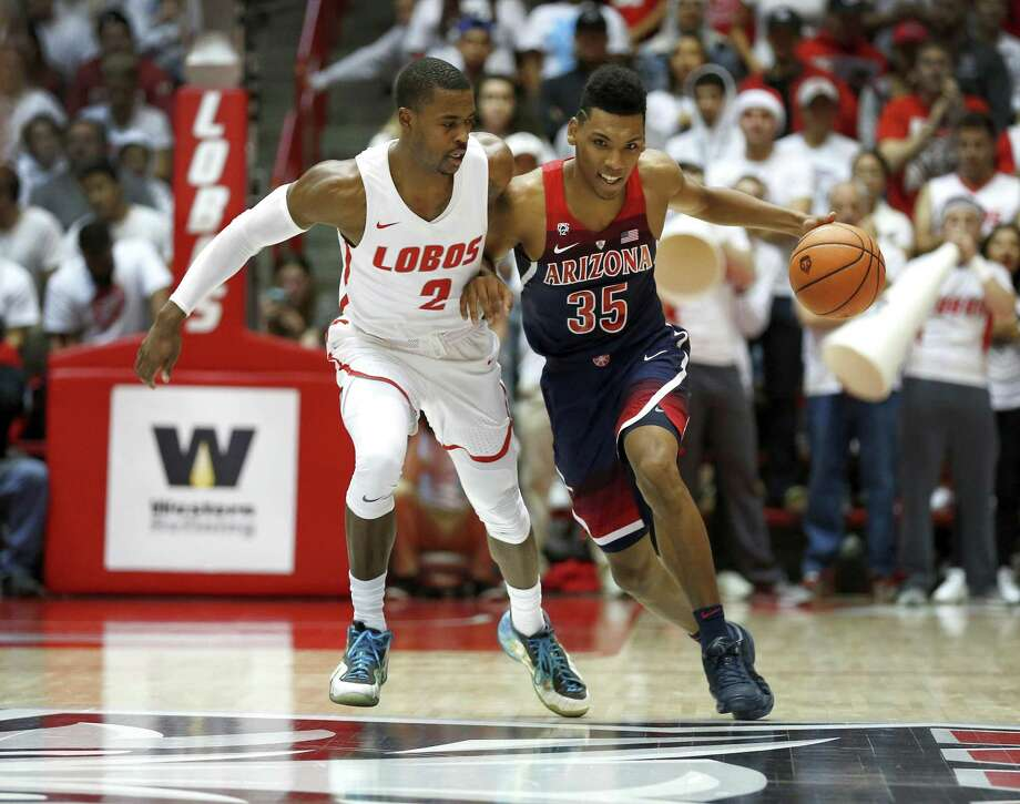 Arizona's Allonzo Trier dribbles past New Mexico's Sam Logwood Saturday in Albuquerque, N.M. Photo: Eric Draper / Associated Press / FR170149 AP